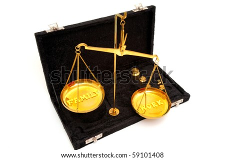 Conceptual image  of the job and family out of balance in a busy and stressful world using a brass  balance scale with yellow letters to spell out the concept
