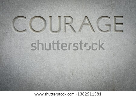 Conceptual Image Of The Word Courage Engraved Into Rock With Copy Space #1382511581