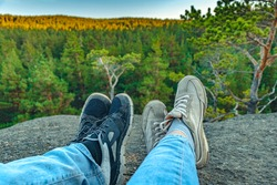 Conceptual image of two pairs of legs in sneakers against the background of forest rock. Casual unisex sneakers and jeans on mountain. Couple on the top of mountain. Life style.