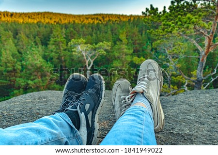 Conceptual image of two pairs of legs in sneakers against the background of forest rock. Casual unisex sneakers and jeans on mountain. Couple on the top of mountain. Life style. Photo stock ©
