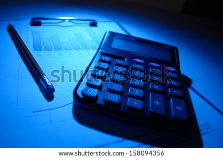 Conceptual image of working overtime with a calculator and pen lying in a shaft of blue light on a clipboard with an attached analytical business graph
