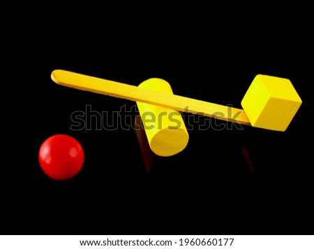 Conceptual image with colorful objects where the cube has outweighed a ball. Stock photo ©