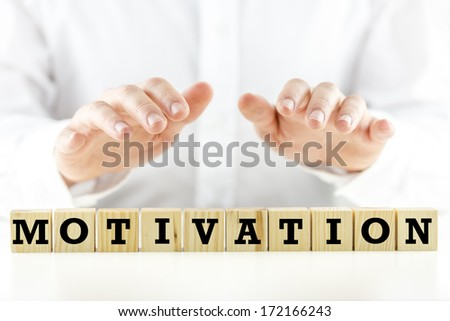 Conceptual image with the word Motivation on wooden blocks or cubes protected by the hands of a man sheltering them from above