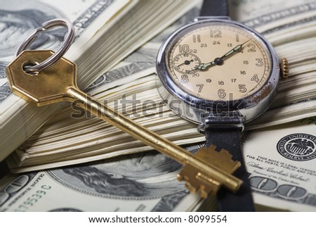 Conceptual keys to success of time and money. Rich colors and clear shot with skeleton key, US currency, a small modern watch that portrays spending, finance, business success.