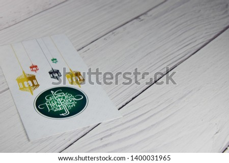 Conceptual money gift for eid ul fitr celebration. Money packet with wish 'Selamat Hari Raya Aidilfitri' is in focus. Wooden background.  #1400031965
