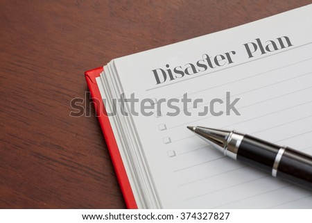 Conceptual,notebook on a wooden table. open diary and pen with disaster plan word #374327827