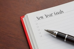 Conceptual,notebook on a wooden table. open diary and pen with new year goals words
