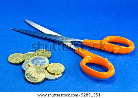 Conceptual of cutting costs with Scissors and coins