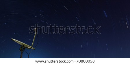 Conceptual of yellow satellite over spiral star at night