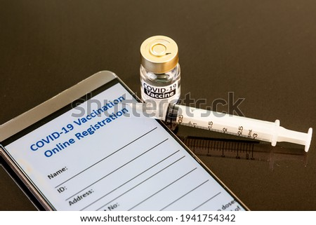 Conceptual online registration for Covid-19 vaccination via smart phone, with vial and syringe as prop Stockfoto ©