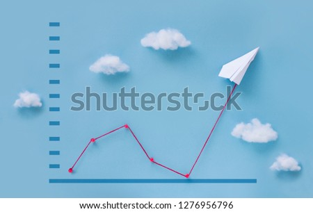 Conceptual paper plane pulling business finance growth chart line upwards on blue sky background.