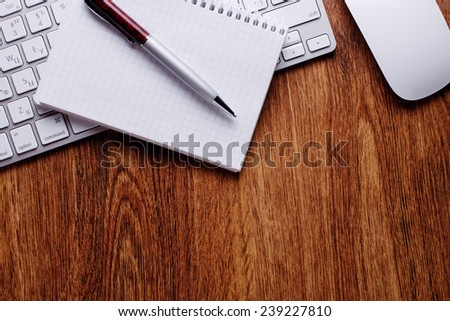 Conceptual Pen and Notes with Computer Keyboard and Mouse on Top of Wooden Table with Copy Space on Bottom.