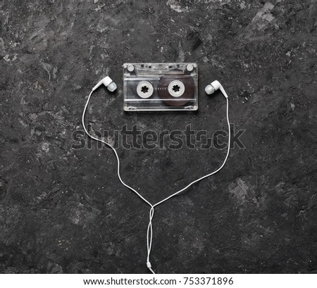 Conceptual photo illustrating the love of music. Audio cassette and headphones on a black concrete background. Top view.
