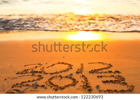 Conceptual photo: New Year 2013 is coming  - inscription 2012 and 2013 on a beach sand