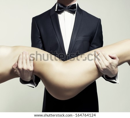 Conceptual photo. Nude lady at the hands of a man in suit - stock photo