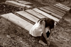 conceptual photo of a grieving woman sitting at a stone with perspective stone alignment in black and white.