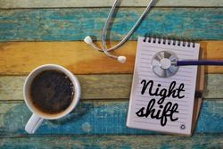 Conceptual photo of coffee, stethoscope and notepad on the vintage background. Night shift among Frontliners during pandemic of Covid-19