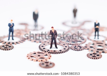 Conceptual photo of gears and toy people. Business, law or political concept, which could represent decision making, leadership, teamwork  and so on.