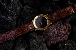 Conceptual photography luxury watch. Gold brown black watch on magma rock background