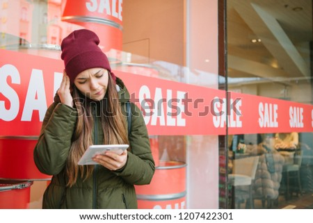 Conceptual photography. The girl chooses online products on sale. Time of off-season and winter sales, Black Friday and Cyber Monday.