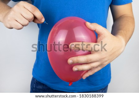 Conceptual photography. The man holds a red ball near his belly, which symbolizes bloating and flatulence. Then he brings a needle to it to burst the balloon and thus get rid of the problem. Stockfoto ©