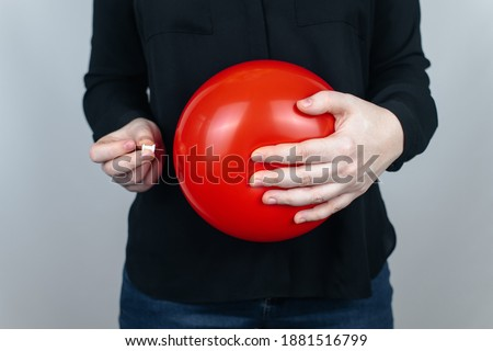 Conceptual photography. The woman holds a red ball near his belly, which symbolizes bloating and flatulence. Then she brings a needle to it to burst the balloon and thus get rid of the problem. Stockfoto ©