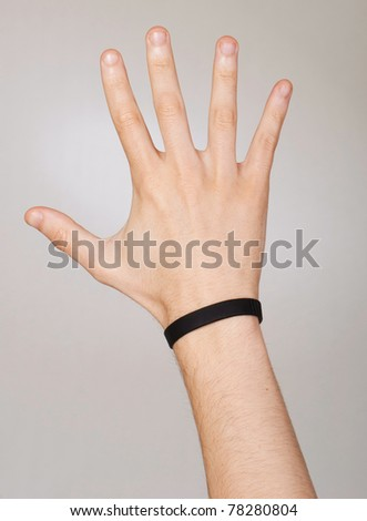 conceptual picture of a photographer hand with bracelet trying to catch the light that come from the background