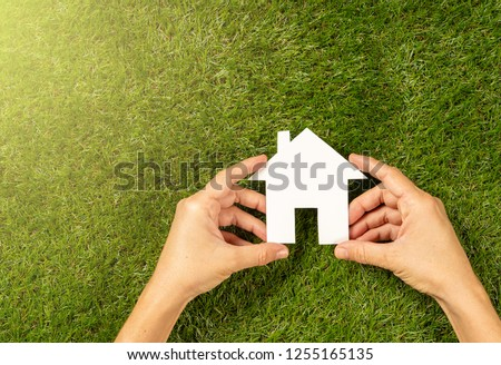 Conceptual picture of woman hands holding white house over green grass field top view and copy space in Property investment Real estate Saving and buying a home mortgage and loan banking concept.