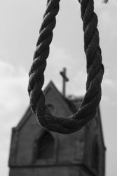 Conceptual picture with hanging gallow rope and church tower with christian cross on the background, black and white