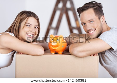 Conceptual portrait of new couple with piggybank on top of the box