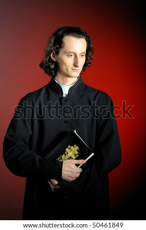 conceptual portrait of Praying priest with  Holy Bible. red background