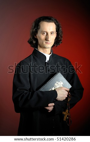 conceptual portrait of Praying priest with wooden cross and Holy Bible. red background - stock photo