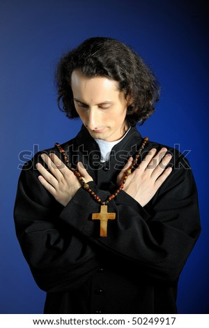 conceptual portrait of Praying priest with wooden cross. blue background