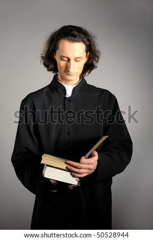 conceptual portrait of Praying priest with wooden cross reading Holy Bible. yellow background