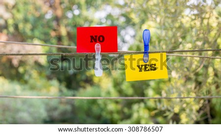 Conceptual Red and Yellow Paper with Yes and No Messages Clipped on a String Against Fuzzy Greenery Background.