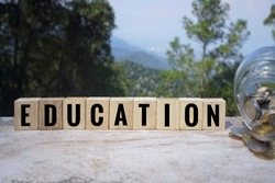 Conceptual. Saving purpose - 'EDUCATION' written on wooden blocks. With blurred styled background.