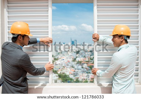 Conceptual shot of business people widening the view on the construction site