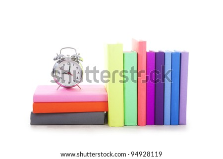 Conceptual-silver alarm clock at 9 over a stack of book