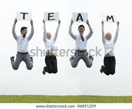 Conceptual Stock image of an Asian man & woman jumping holding sign