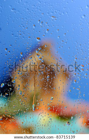 Conceptual stock photo of an Out of focus country house under blue sky behind wet glass in rainy weather
