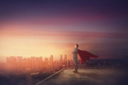 Conceptual sunset scene, business person with red cape stands confident on rooftop looking determined as a superhero over city horizon. Ambition and leadership success concept. Hero power, motivation.