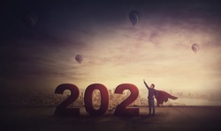 Conceptual sunset scene, creative business person with red cape, looks determined as a superhero, stands confident on rooftop beside big numbers, creates the shape of 2021 new year. Hero leadership.