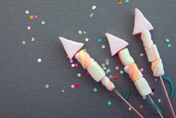 Conceptual Sweet Marshmallow Forming Rocket Fireworks on Gray Cloth Background with Attractive Colored Sequence.