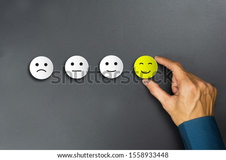 Conceptual the customer responded to the survey. The client using hand choose happy face smile icon. Depicts that customer is very satisfied. Service experience and satisfaction concept. Stockfoto ©