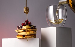 Conceptual view of pancakes with berries and honey and green tea pouring into glass mug.