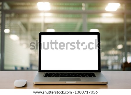 Conceptual workspace,Laptop with blank white screen and wireless mouse on wooden desk,In office blurred background of bokeh. - Image