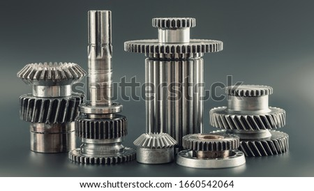 Conceptually mechanical background. Gears of gear shifting torque transmission. Shiny chrome gear. Gearing of drive mechanism of machine tool. New parts, gear teeth on black background closeup