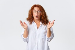 Concerned and ambushed redhead female in glasses, middle-aged woman react to shocking news, raising hands up and gasping worried, feeling alarmed about situation, white background