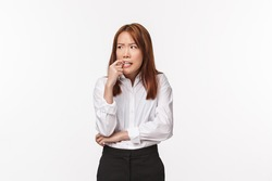 Concerned and anxious young asian woman biting her nails and looking around as feeling nervous, worried about something, thinking about consequences of bad decision, white background