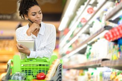 Concerned Black Lady Thinking Buying Food And Calculating Increased Food Prices Standing In Supermarket, Having Financial Issues During Crisis. Discontented Female Buyer In Food Shop. Empty Space